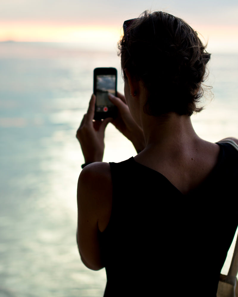 Girl taking a photo of the ocean